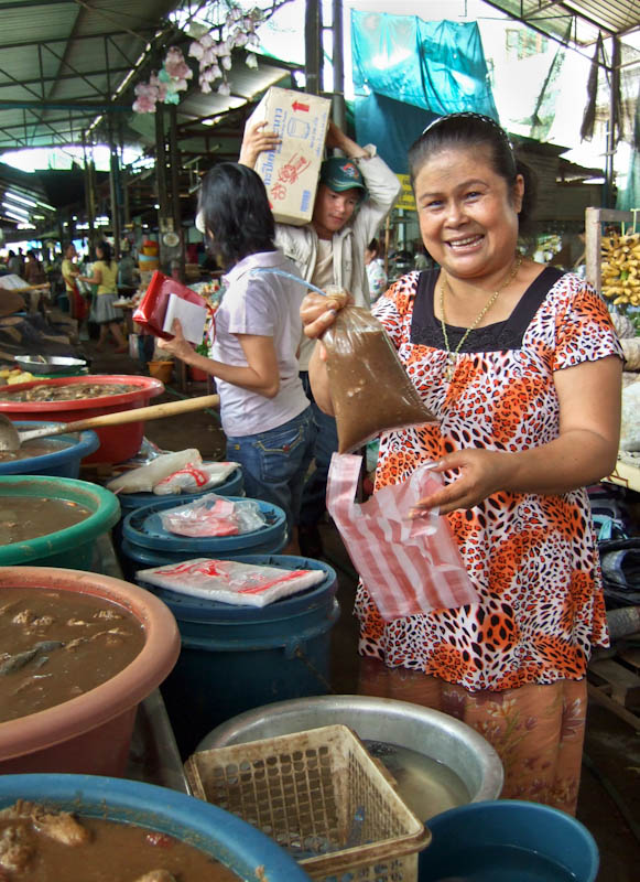 Padek seller preparing a plastic bag of padek for customer