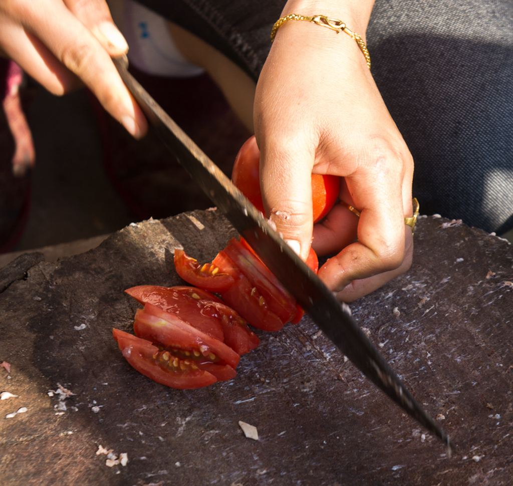 Slicing tomatoes for adding to the meat paste
