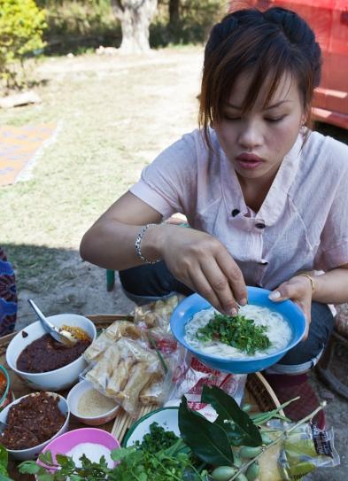 Nang Buawon preparing a bowl of khao soi noodles