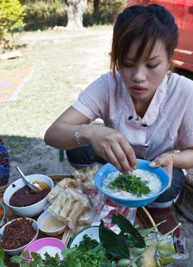 Nang Buawon preparing a bowl of khao soi noodles